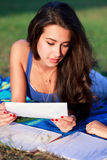 Pretty College Teenager Studying Outdoor. Pretty multiracial college teenager studying outdoors on a university campus field Stock Images
