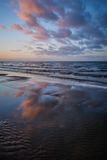 Pretty color dawn sunset in Latvia. The pretty colours of dawn sunset in the sky and clouds and reflections in the water at Vakarbulli beach in Latvia Stock Image