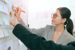 Pretty company manager lady holding red pen. Smiling pretty company manager lady holding red pen writing note on paper and colleague pointing report content to royalty free stock images