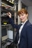 Pretty computer technician smiling at camera while fixing server Stock Photography