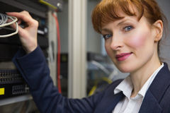 Pretty computer technician smiling at camera while fixing server Royalty Free Stock Image