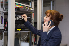 Pretty computer technician talking on phone while fixing server Royalty Free Stock Photography