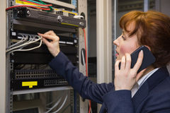 Pretty computer technician talking on phone while fixing server Royalty Free Stock Images