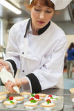 Pretty concentrating head chef preparing dessert Royalty Free Stock Images