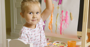 Pretty confident little girl painting at home Stock Images