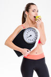 Pretty content sportswoman eating apple and holding weighing scale Royalty Free Stock Photo