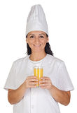 Pretty cook girl with a glass of orange juice Stock Images