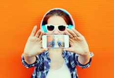 Pretty cool girl makes self-portrait on the smartphone Royalty Free Stock Images