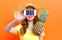 Pretty cool girl with pineapple taking picture self portrait on smartphone stock photos