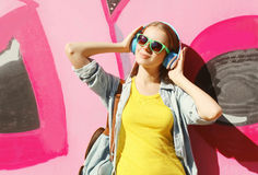 Pretty cool girl wearing a sunglasses, headphones listens to music in city Stock Images