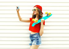 Pretty cool smiling girl makes self portrait on smartphone over white Stock Image