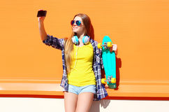 Pretty cool smiling girl in sunglasses with skateboard taking picture self portrait on smartphone Royalty Free Stock Photography