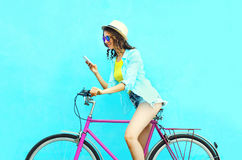 Pretty cool smiling woman using smartphone on retro bicycle over colorful blue background Royalty Free Stock Images