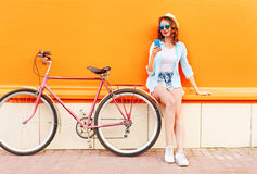 Pretty cool smiling young woman using smartphone with retro bicycle over colorful orange Stock Photography