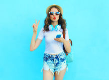 Pretty cool woman listens music and using smartphone over colorful blue Stock Photography