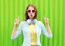 Pretty cool woman listens to music in headphones over green Stock Photo