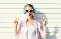 Pretty cool woman listens to music in headphones over white Royalty Free Stock Image