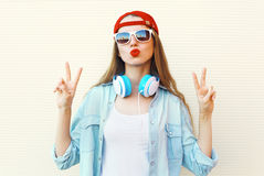 Pretty cool woman in sunglasses and red cap having fun over white Royalty Free Stock Images