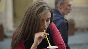 Pretty coquette sits in a street cafe with drink and smiles at camera stock footage