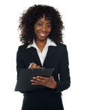Pretty corporate woman writing on clipboard Stock Photo