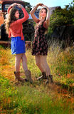 Pretty Country Girls. Two happy teenaged country girls with long brown hair, dancing and laughing together. Shallow depth of field Royalty Free Stock Photos