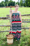 Pretty country woman with wooden rake and bucket Royalty Free Stock Images