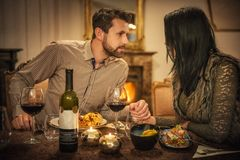 Pretty couple drinking red wine and eating in restaurant, winter time, romantic dinner royalty free stock photography