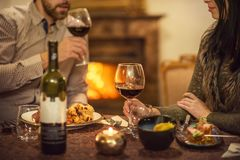 Pretty couple drinking red wine and eating in restaurant, winter time, romantic dinner stock photo