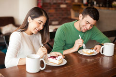 Pretty couple eating some dessert. Happy young couple eating a slice of pie at a coffee shop Royalty Free Stock Photography