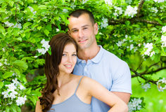 Pretty couple embracing near blossomed tree Royalty Free Stock Photos