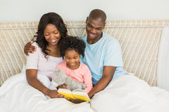 Pretty couple with her daughter reading a book in bed Stock Photography