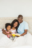 Pretty couple with her daughter reading a book in bed Stock Image