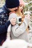 Pretty couple with hot tea in cups in forest Royalty Free Stock Photos