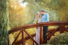 Pretty couple hugging and flirting in an urban park. Standing on the bridge and look at each other a wreath on his head, holding flowers in their hands summer Royalty Free Stock Image