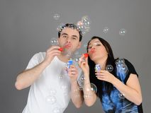 Pretty couple in love blowing bubbles Stock Images