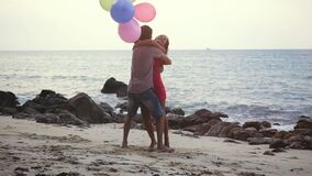 Pretty couple in love run to each other holding multicolored balloons hugging spin around have enjoying vacation on stock video footage