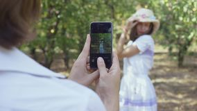 Pretty couple in love spending time together in the park. The man taking photo of pretty woman in hat. Lovers have fun. Cute couple spending time together in the stock footage
