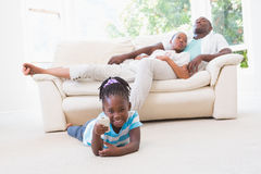 Pretty couple sitting on couch and their daughter playing Royalty Free Stock Images