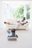 Pretty couple sitting on couch and their daughter using laptop Stock Photos