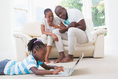 Pretty couple sitting on couch and their daughter using laptop Royalty Free Stock Images