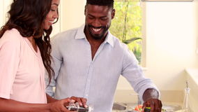 Pretty couple smiling and cooking stock video
