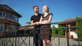 Pretty couple standing together on brick terrace of their lakehouse, beautiful landscape around stock video