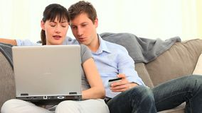 Pretty couple using a credit card on internet Stock Photos