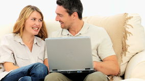 Pretty couple using a laptop stock footage
