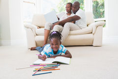Pretty couple using laptop on couch and their daughter drawing Stock Photo