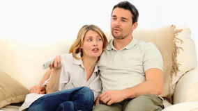 Pretty couple watching tv stock video