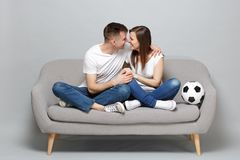 Pretty couple woman man football fans cheer up support favorite team with soccer ball, looking at each other isolated on royalty free stock photo