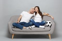 Pretty couple woman man football fans in white t-shirt cheer up support favorite team with soccer ball, hugging isolated. Pretty couple women men football fans royalty free stock photos