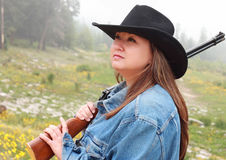 Pretty Cowgirl with Rifle. Portrait of pretty woman in black cowboy hat holding a rifle Royalty Free Stock Photo