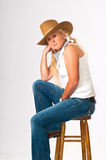 Pretty cowgirl seated on a stool Stock Photos
